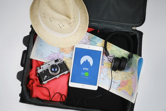 Travel bag with a map, straw hat, camera, smartphone and headphones