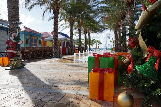 A walkway with palm trees and Christmas presents, bells and Santa Claus.