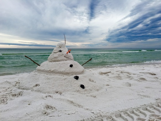 A snowman made from white sand on the beach in tropics.