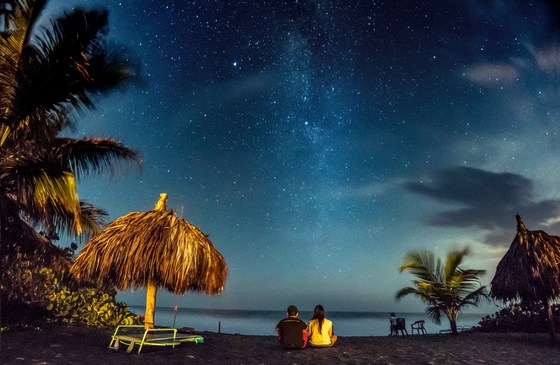A couple on a tropical beach under the sky full of stars