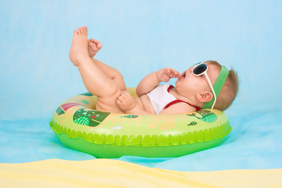Baby with sunglasses laying on an inflatable
