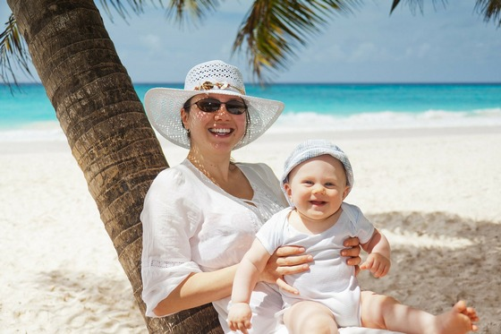 Smiling mum and baby on a tropical beach under a palm