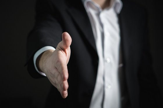 A person in a suit offering a hand for a handshake.